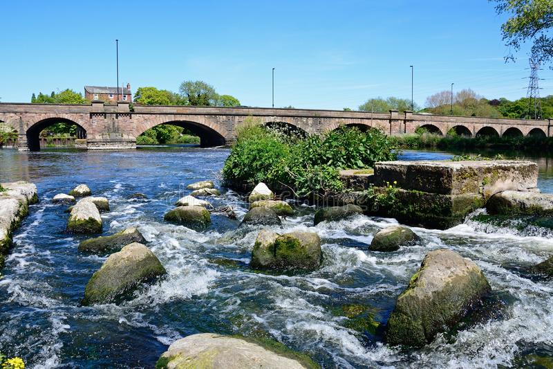 River Trent and Trent Bridge, Burton upon Trent. View across boulders and the weir towards the Trent Bridge road bridge A511 over the River Trent, Burton upon stock photos