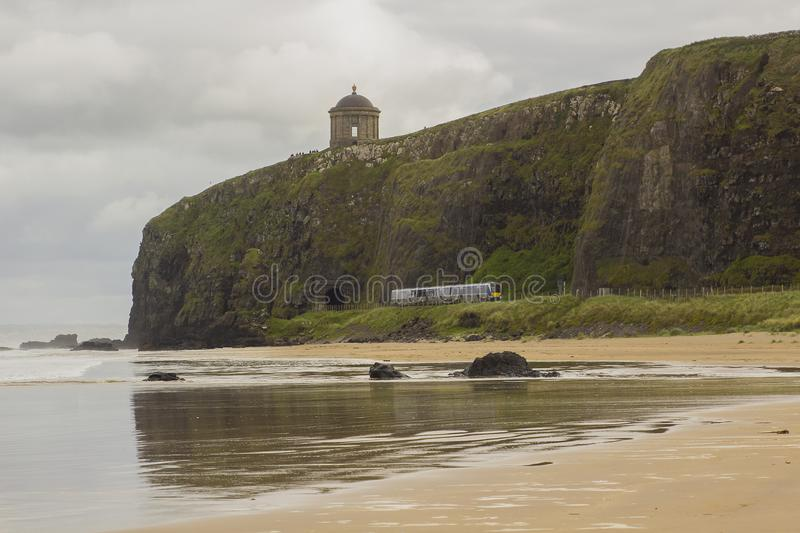 A view across Downhill beach in County Londonderry in Northern Ireland with a train heading toward the cliff tunnel stock images