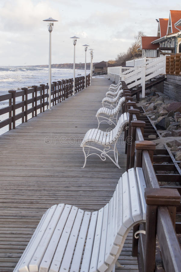 View across and empty deserted row of benches at the end of the pier looking towards the promenade royalty free stock images