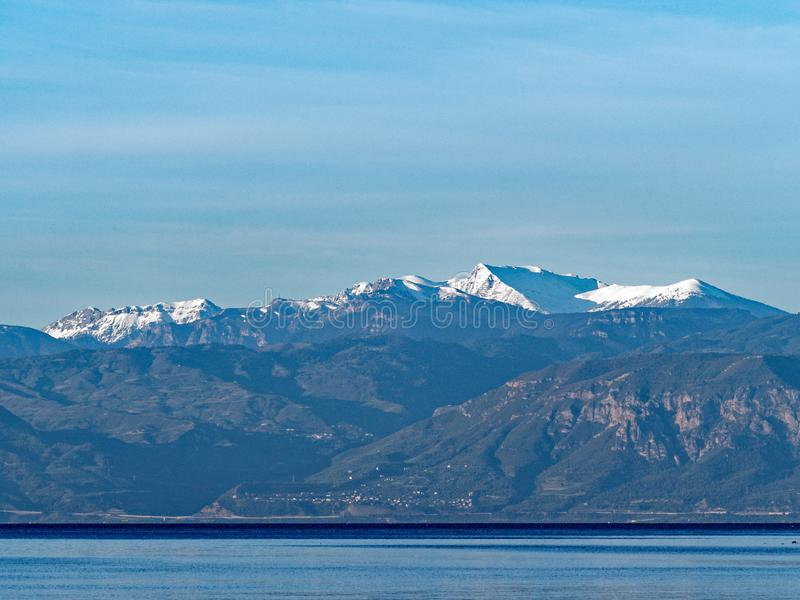 View Across Gulf of Corinth to Snow Capped Peloponnese Mountain, Greece. View South across calm Corinthian Gulf sea water to fresh Spring snow on Peloponnese royalty free stock image