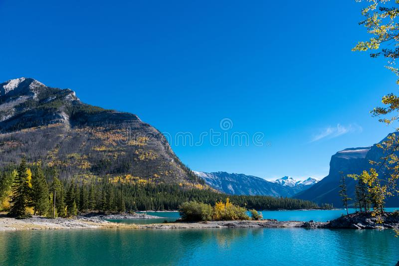 A view across placid Lake Minnewanka in Banff National Park on a clear September morning. BANFF NATIONAL PARK, CANADA / SEPTEMBER 13, 2016:  A view across placid stock photography