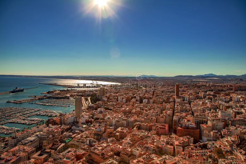 Aerial view over the rooftops and Alicante harbor Spain. View across the rooftops in Alicante, Valencia province, Spain looking towards mountains over the royalty free stock image