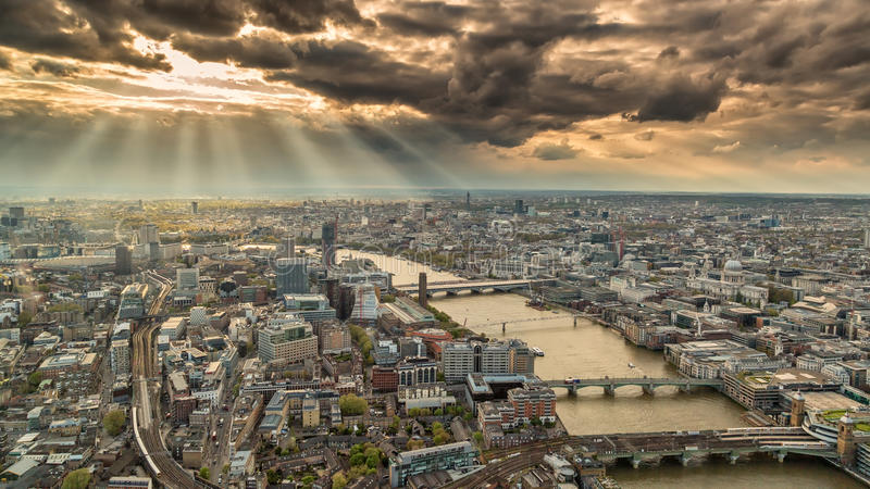 View across the skyline of London with moody skies. Overhead view of the skyline of London in England with the river Thames against a moody and cloudy sky with stock images
