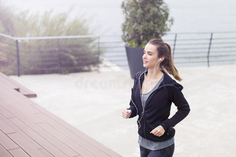 Active young beautiful woman running in urban enviroment royalty free stock photo