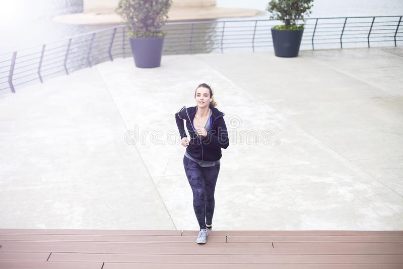 Active young beautiful woman running in urban enviroment stock photos
