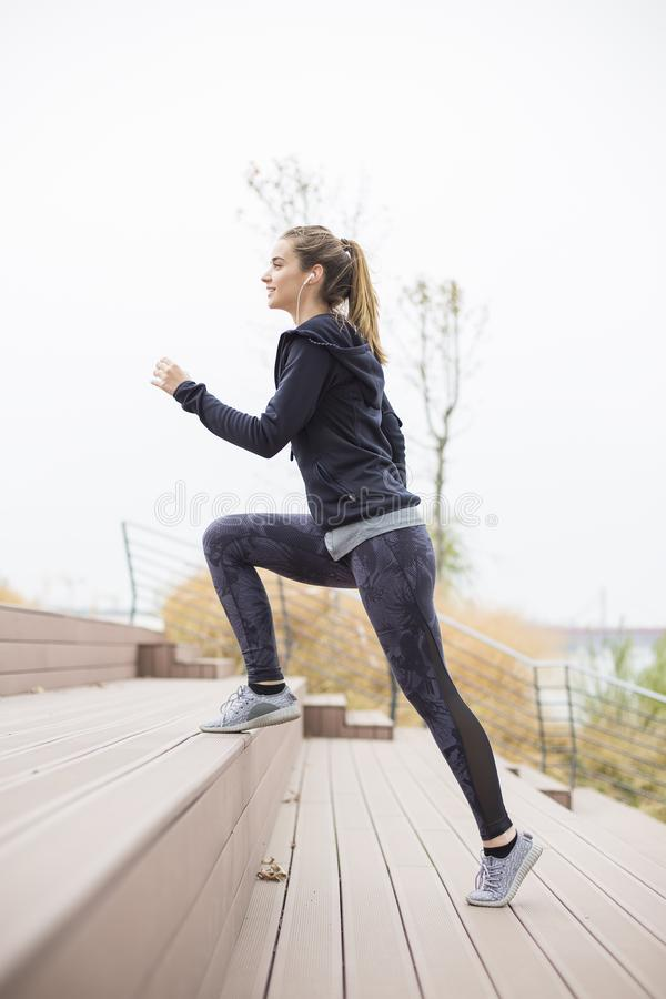 Active young beautiful woman running in urban enviroment stock photo