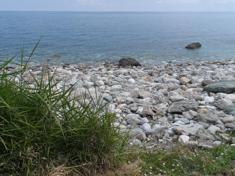 View of the Aegean sea, early June, cloudy day. Grass, stones royalty free stock photos