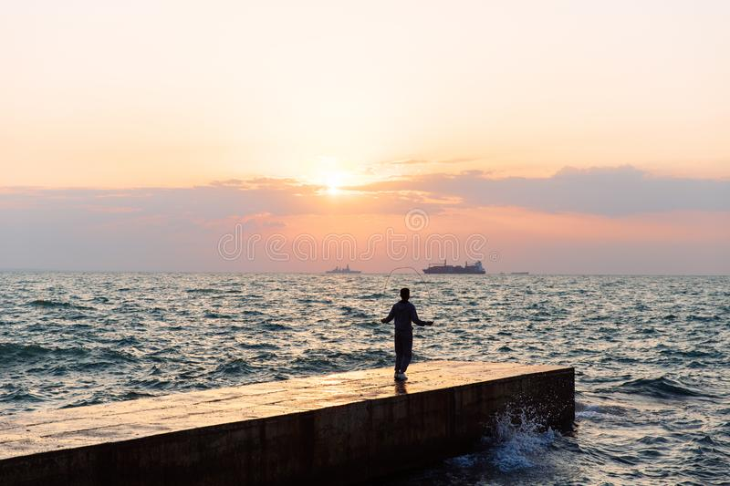View from afar on sportsman with skipping rope, jumping on pier. Full length view of young sportsman jumping with skipping rope, on pier, near the sea. Sunset stock photo