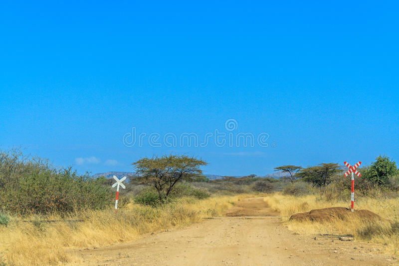 A view of african savannah and road signs. A view of African Savannah. Two traffic sign for railway and a dirt road is on the photo stock images