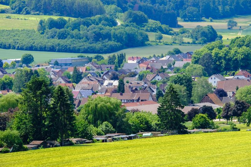 View on the agricultural fields with grain and houses in Bad Pyrmont in Germany. View on the agricultural fields with various types of grain and a villagy with stock photography