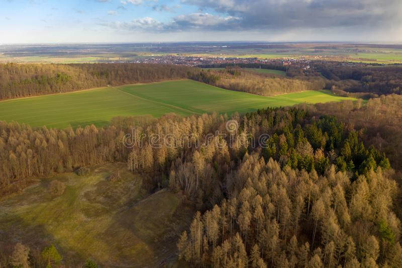 View from the air over a deciduous forest in Northern Germany with a large meadow area switched on and a village in the background.  royalty free stock photography