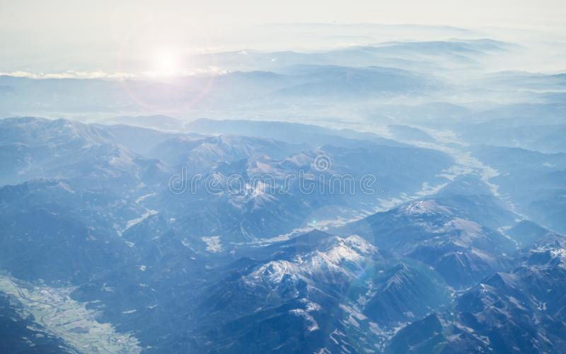 View from the aircraft on the Alps. Spectacular views of the sunrise and the mountain peaks in snow, blue tinted glass and the royalty free stock image