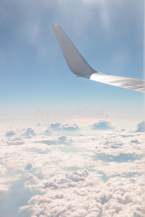 View from airplane, carrier wing and glorious blue sky with beautiful cumulus of white clouds. Vacation, travel with stock image