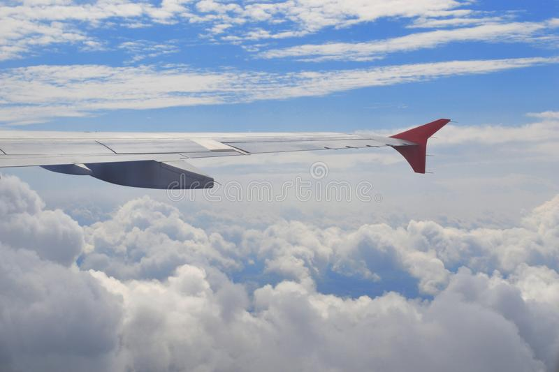 View from airplane illumination above the clouds. Wing of plane above cloudy sky in sunny day. Concept of travel, freedom, dreams stock photography