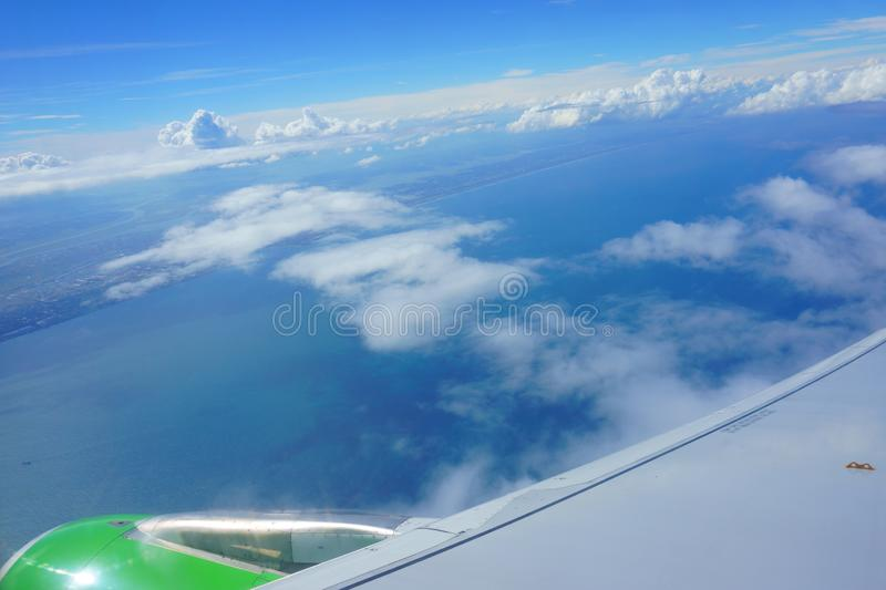 View from airplane porthole. blue sky, sea, coast, wing of plane stock image