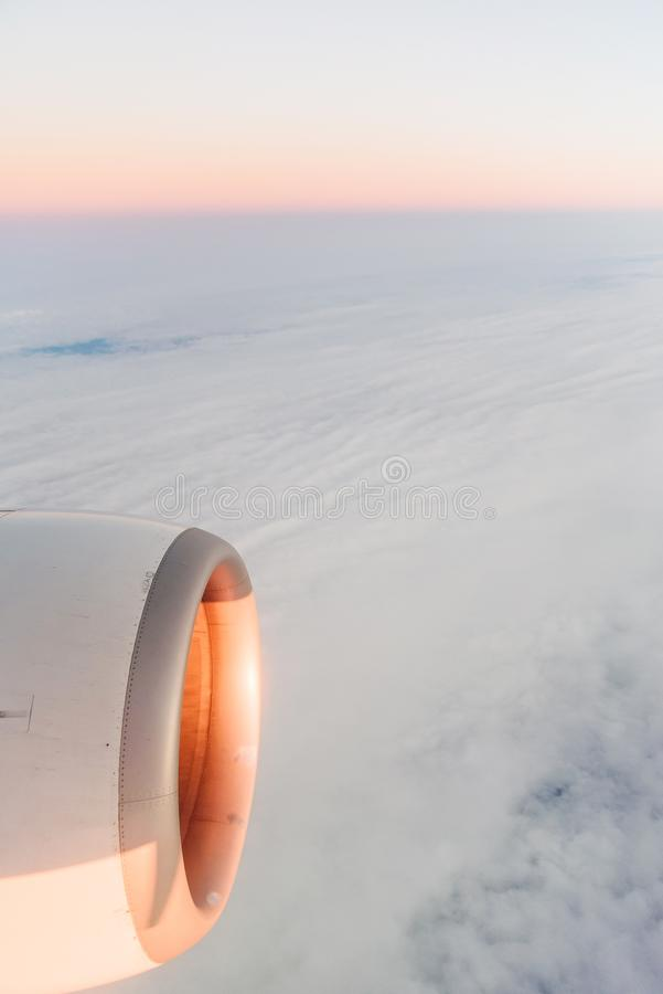 The view from the airplane`s illuminator to the wing, airplane turbine and fluffy clouds at sunrise. Flying over the royalty free stock photo