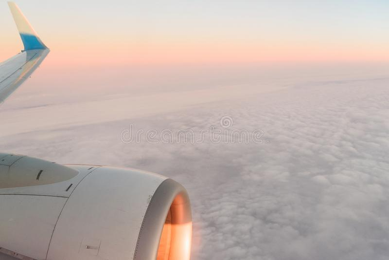 The view from the airplane`s illuminator to the wing, airplane turbine and fluffy clouds at sunrise. Flying over the. Clouds stock photography