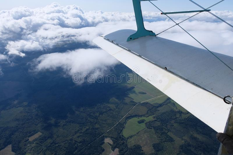 A view from airplane`s opened door. Aviation. An airplane is in the sky. The view from opened door.  A wing of the airplane and pretty clouds royalty free stock photos