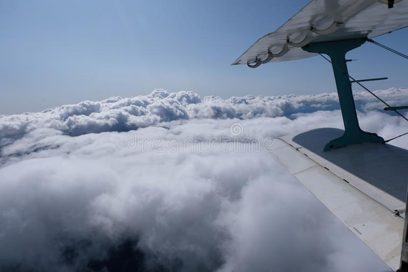 A view from airplane`s opened door. Aviation. An airplane is in the sky. The view from opened door.  A wing of the airplane and pretty clouds stock photos
