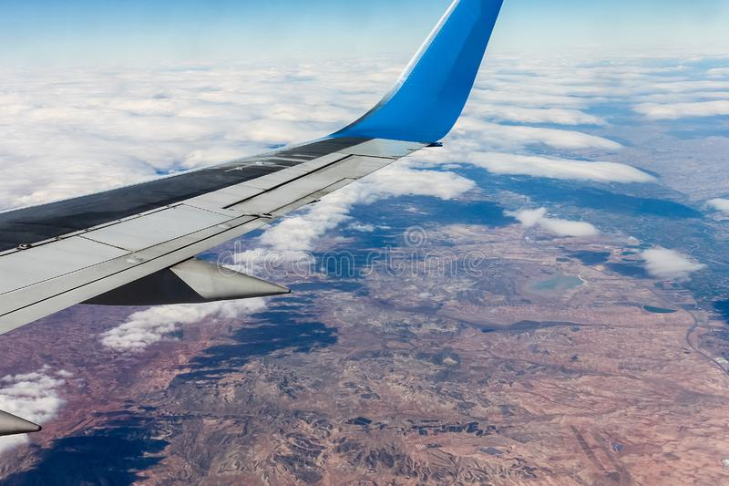View from airplane window with clouds and land. Time  to travel. Clouds, land, sky as seen through window stock image