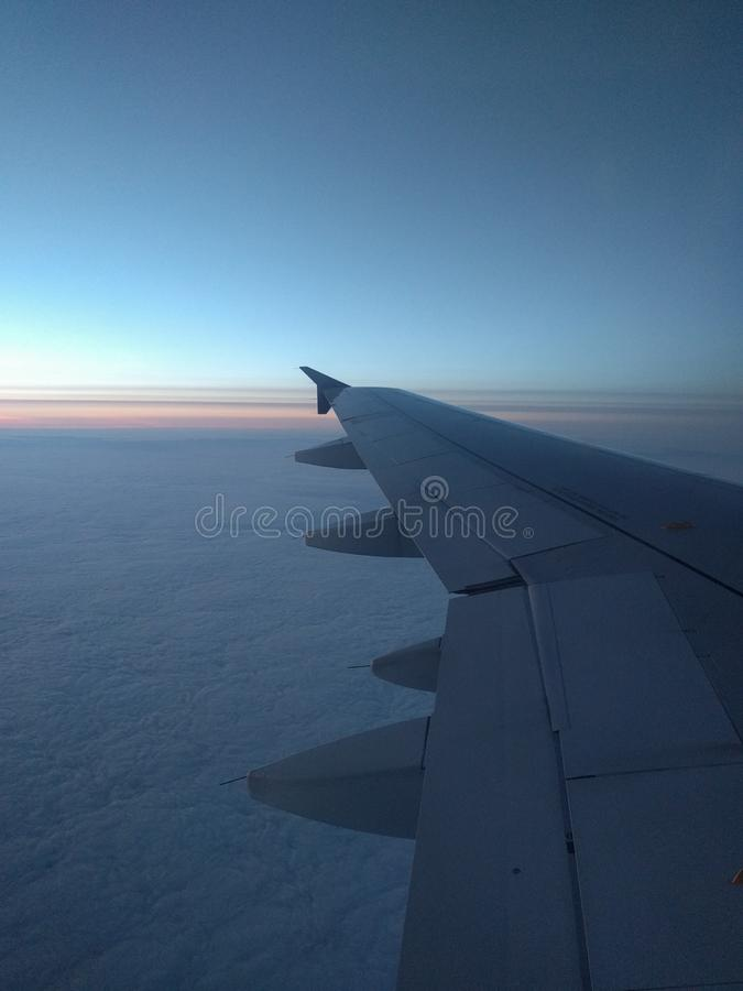 View from airplane window to beautiful sunrise or sunset. Wing of plane and clouds in the sky royalty free stock photo