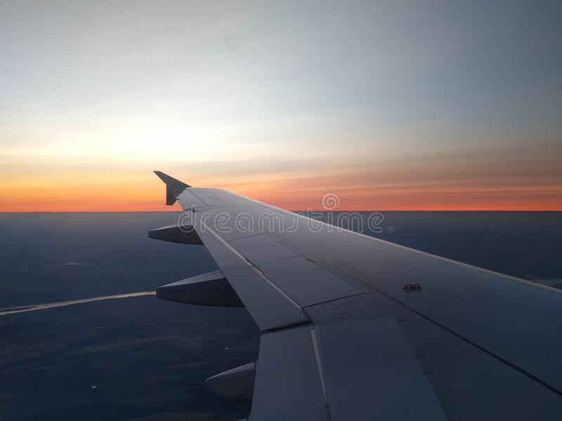 View from airplane window to beautiful sunrise or sunset. Wing of plane flying above in the sky royalty free stock image