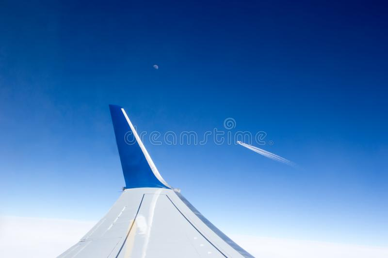 View from the airplane window to the wing and another plane flying by in the distance. royalty free stock photos