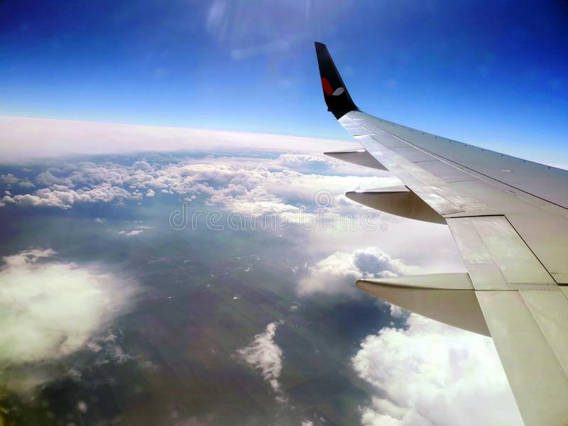 View from airplane window on the wing, clouds and sky.  stock image
