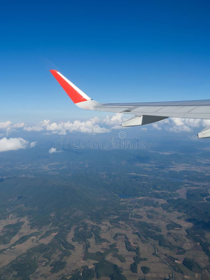 View from airplane windows from passenger, beautiful cloud group, blue sky and landscape. Wing aircraft in altitude during flight. Concept of travel and stock photography
