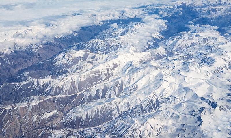 View of airplane wtop view of Afghanistan mountains covered with royalty free stock photography