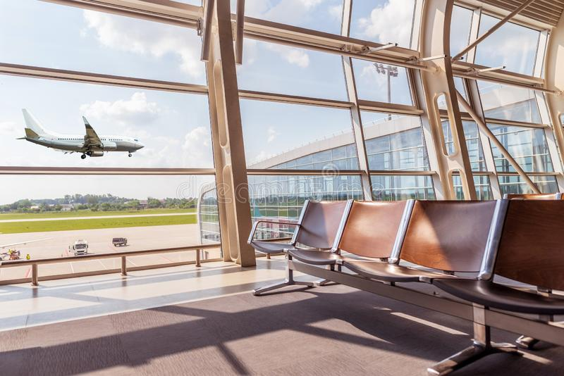 View from the airport lounge to landing aircraft, Car airfield maintenance at airport apron. Airplane travel concept royalty free stock photography