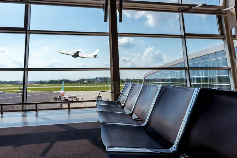 View from the airport lounge to plane taking off, passenger aircraft in the sky. Airplane travel concept royalty free stock photo