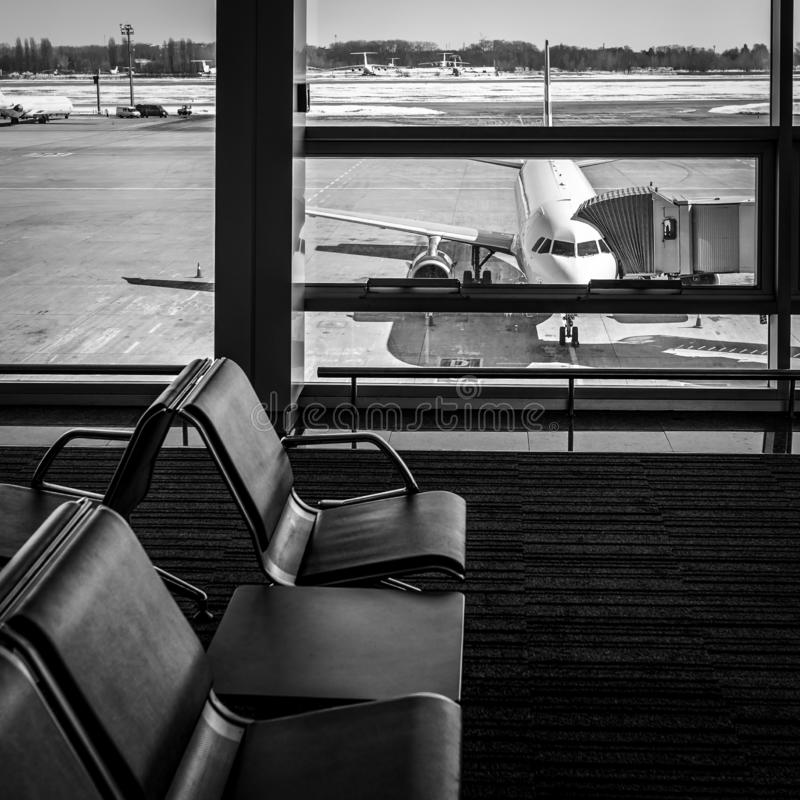 View from the airport terminal to the passenger aircraft with a boarding gate at the airport apron. Airplane travel. View from the airport terminal to the royalty free stock image
