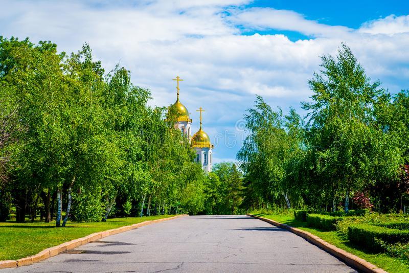View of alley leading to small modern Orthodox church in Russia stock photography