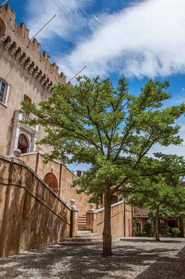 View of alley with trees and facade of the Grimaldi Castle in Haut-de-Cagnes. View of alley with trees and facade of the Grimaldi Castle in Haut-de-Cagnes, a stock photo