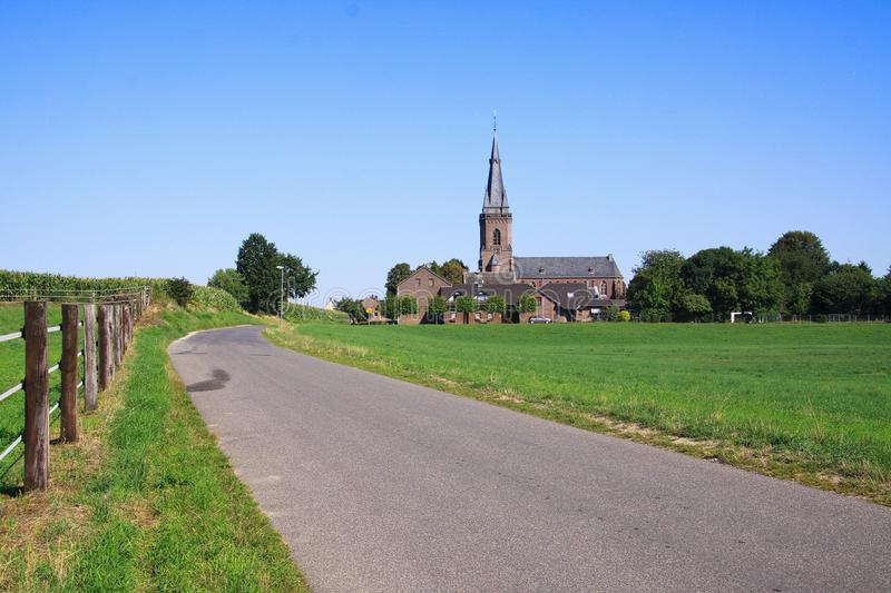 View along agricultural path over green fields on  neo-gothic church in countryside. Viersen Dornbusch, Germany stock photos