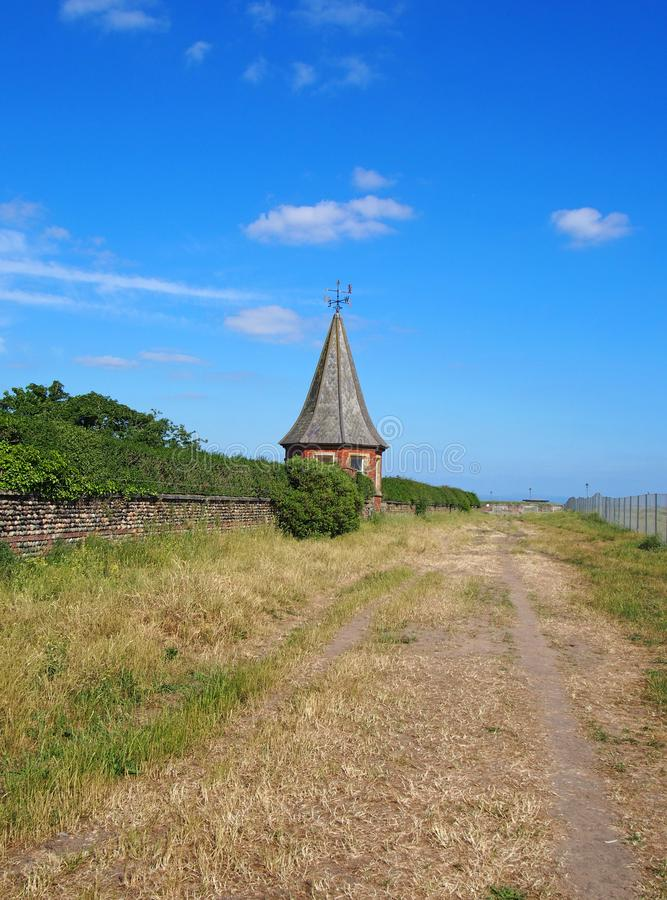 Free View Along Country Straight Lane With A Stone Wall At The Side With An Old Pointed Roofed Building With A Weather Vane On A Su Stock Photo - 124134170
