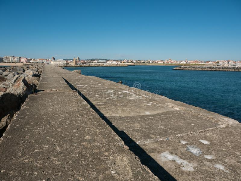 View along harbor wall in Povoa de Varzim, Portugal with sea and harbor on right and city in distance. Bright sunny summer day with blue sky stock image