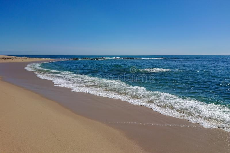 View along shoreline of empty sandy beach in Portugal on a sunny summer day with blue sky, stock photo