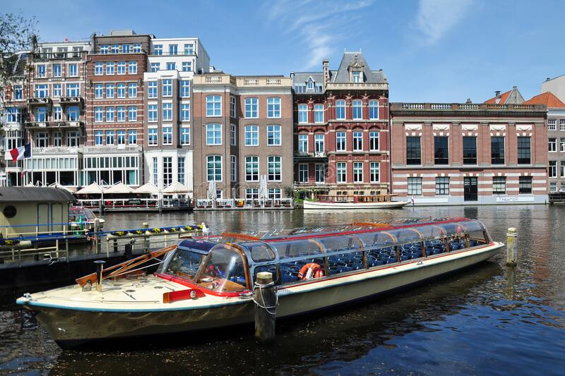 View of the Amsterdam canal with Dutch houses & tourist boat, Netherlands stock images