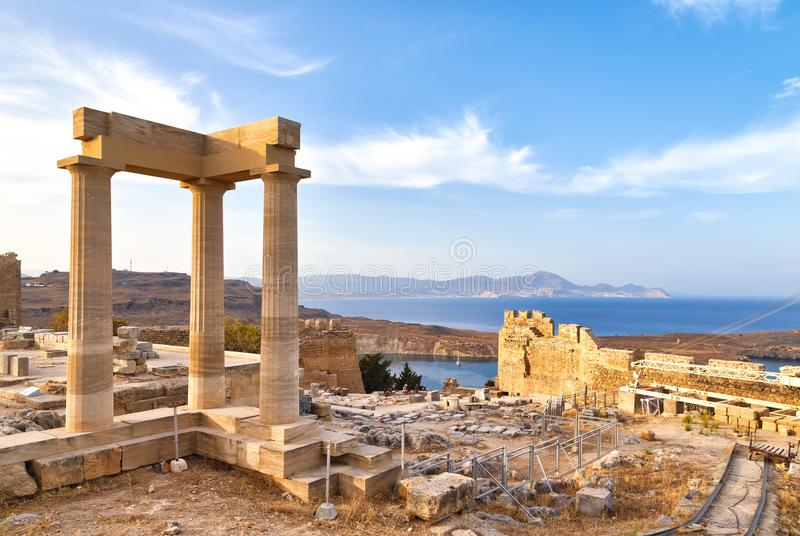 View of the ancient porticos of the temple of goddess linda in Lindos, Rhodes Greece, overlooking the mountains and a surprisingly. Beautiful bay royalty free stock image