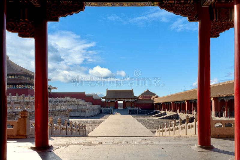 View through an ancient red gate with gold decorations to the square with historical buildings.The Imperial Palace in Beijing royalty free stock images