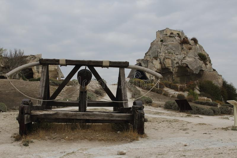 Les Baux-de-Provence, France - OCTOBER 21, 2017: View of the ancient siege weapon against the medieval castle royalty free stock image