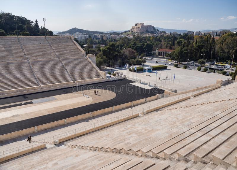 View of the ancient stadium of the first Olympic Games in white marble - Panathenaic Stadium - overlooking the Acropolis and the. Parthenon in the city of royalty free stock image