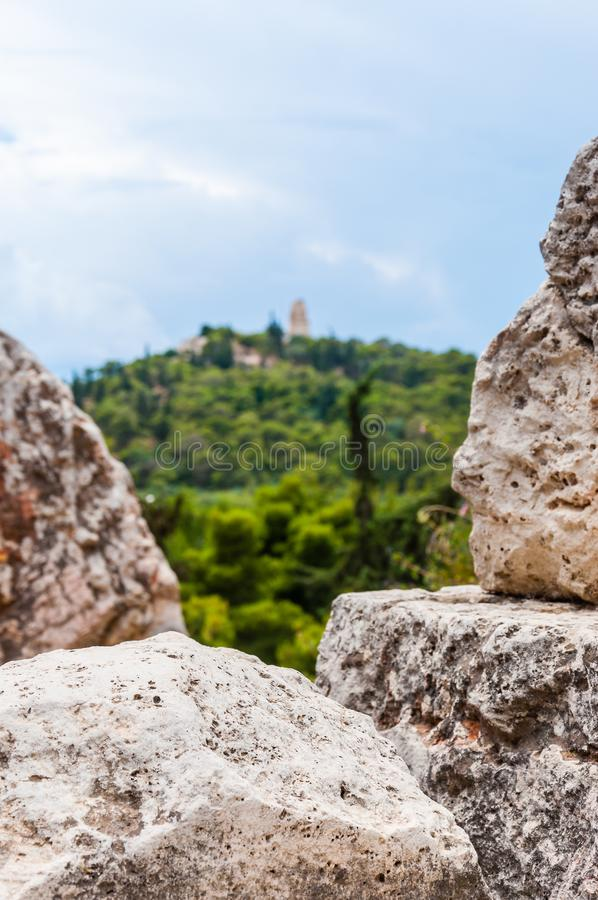 View through the ancient stones on the hill on another hill which overgrown with green flora. View through the ancient stones on the hill on another hill which royalty free stock photography