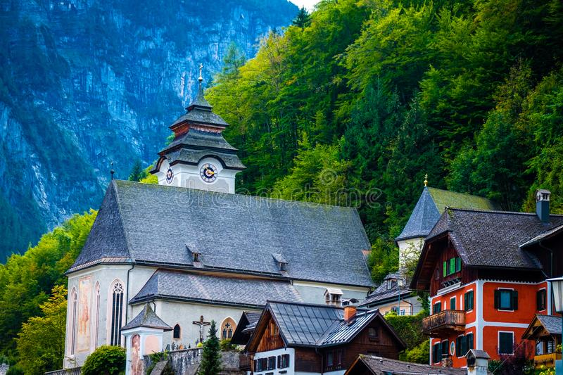 View of anient church and wooden houses at the green forest in Hallstatt, Austria. View of anient church and wooden houses at the green forest of mountain hill royalty free stock photo