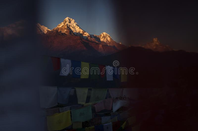 View of Annapurna South at sunset from Poon Hill with buddhist flags. Himalaya Mountains, Nepal royalty free stock photography
