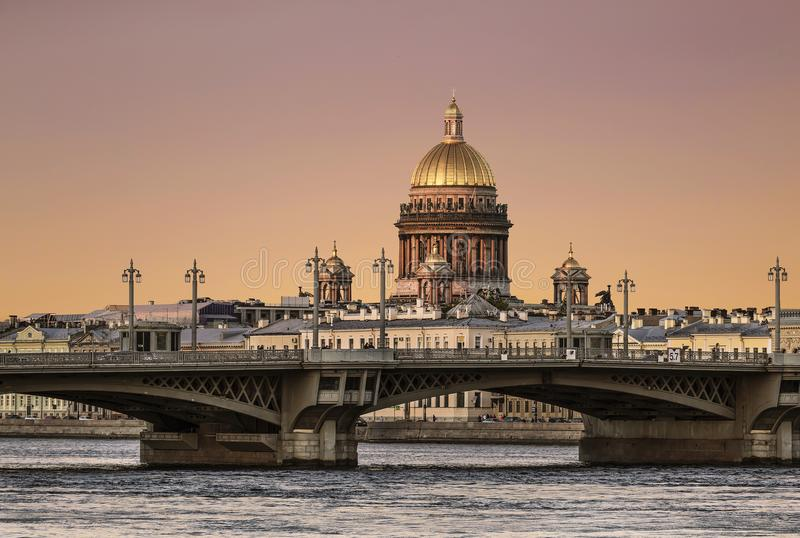 View of the Annunciation bridge across the Neva river and the dome of St. Isaac`s Cathedral at sunset. Saint Petersburg stock image