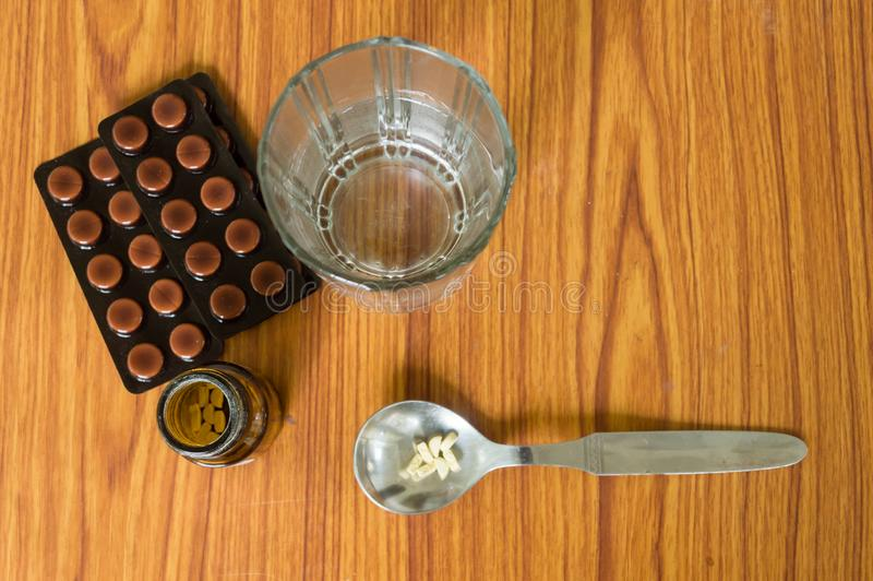 View of antioxidants vitamin tablet, pill blisters, a bottle of drug, capsule in measuring spoon, with glass of water placed on. The table. Medical Pharmacy stock photos