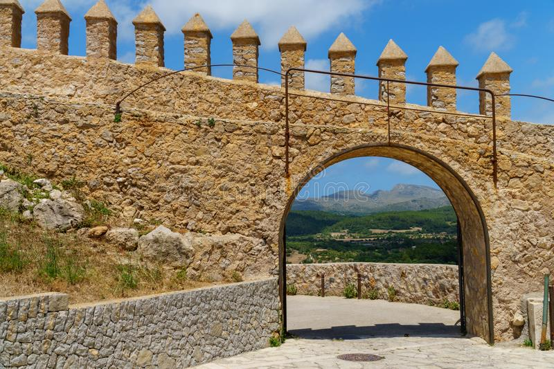 View through an arch in a brick wall at a beautiful landscape in Arta, Majorca. Open gate in a brick wall allows a beautiful view to a distant landscape of stock photo